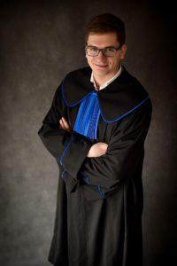 Radca prawny a adwokat - na zdjęciu radca prawny Mateusz Łangowski w todze z niebieskim żabotem odróżniającym od adwokatów, którzy mają żabot w kolorze zielonym. Oba zawody zaliczają się do zawodów prawniczych.